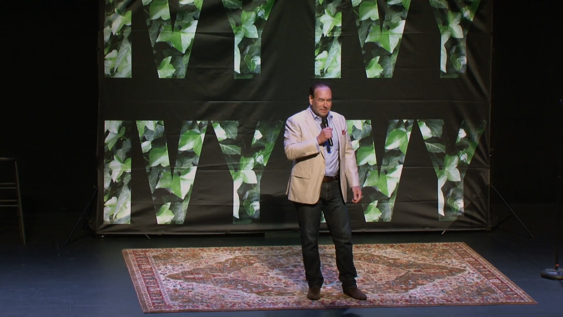 comedian Shaun Eli on stage in front of Ivy logo banner